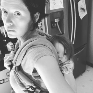 black and white photo of mom wearing baby in soft structured carrier