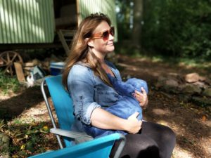 Mom with brown hair and sunglasses sitting on chair outside nursing baby