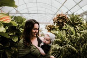 Mom babywearing infant child inside greenhouse