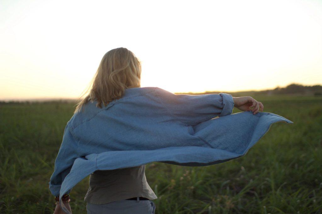 woman walking through field wearing denim shirt