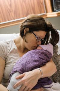 mother kissing newborn head