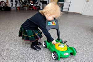 toddler playing with toy lawnmower on polyurea garage floor