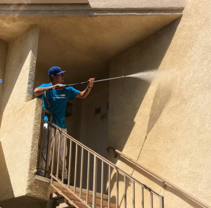 an allbright employee power washing the side of a building