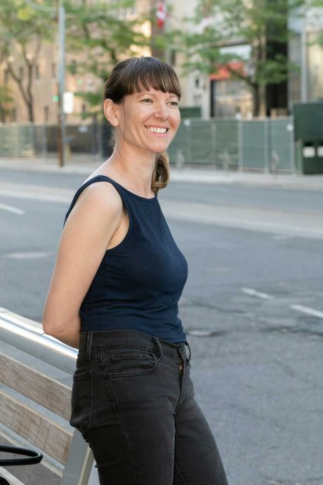 Photo of Sabourin Web & Media digital marketing agency owner Carolyn Sabourin standing near a bus bench outside in the summer. She's a smiling woman with brown hair wearing a navy tank top and black jeans.