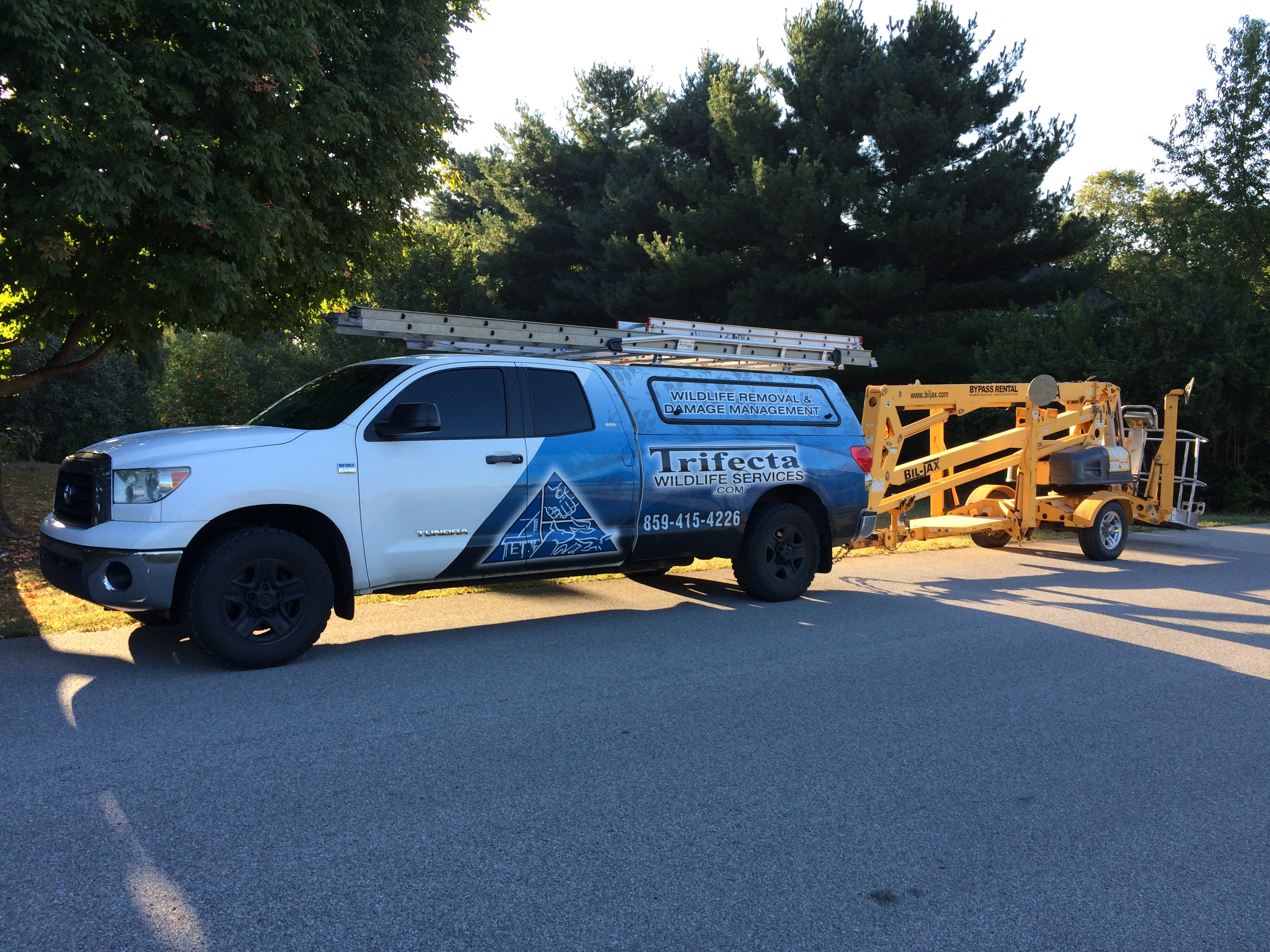 Trifecta Wildlife truck with aerial lift in tow