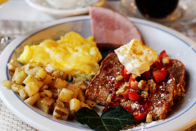 A plate with Strawberry French Toast, Scrambled eggs, seasoned potatoes and ham