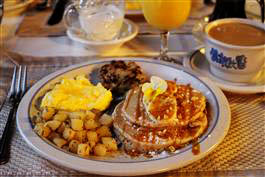 A plate of Cinnamon Chip Pancakes with scrambled eggs, Potatoes and sausage