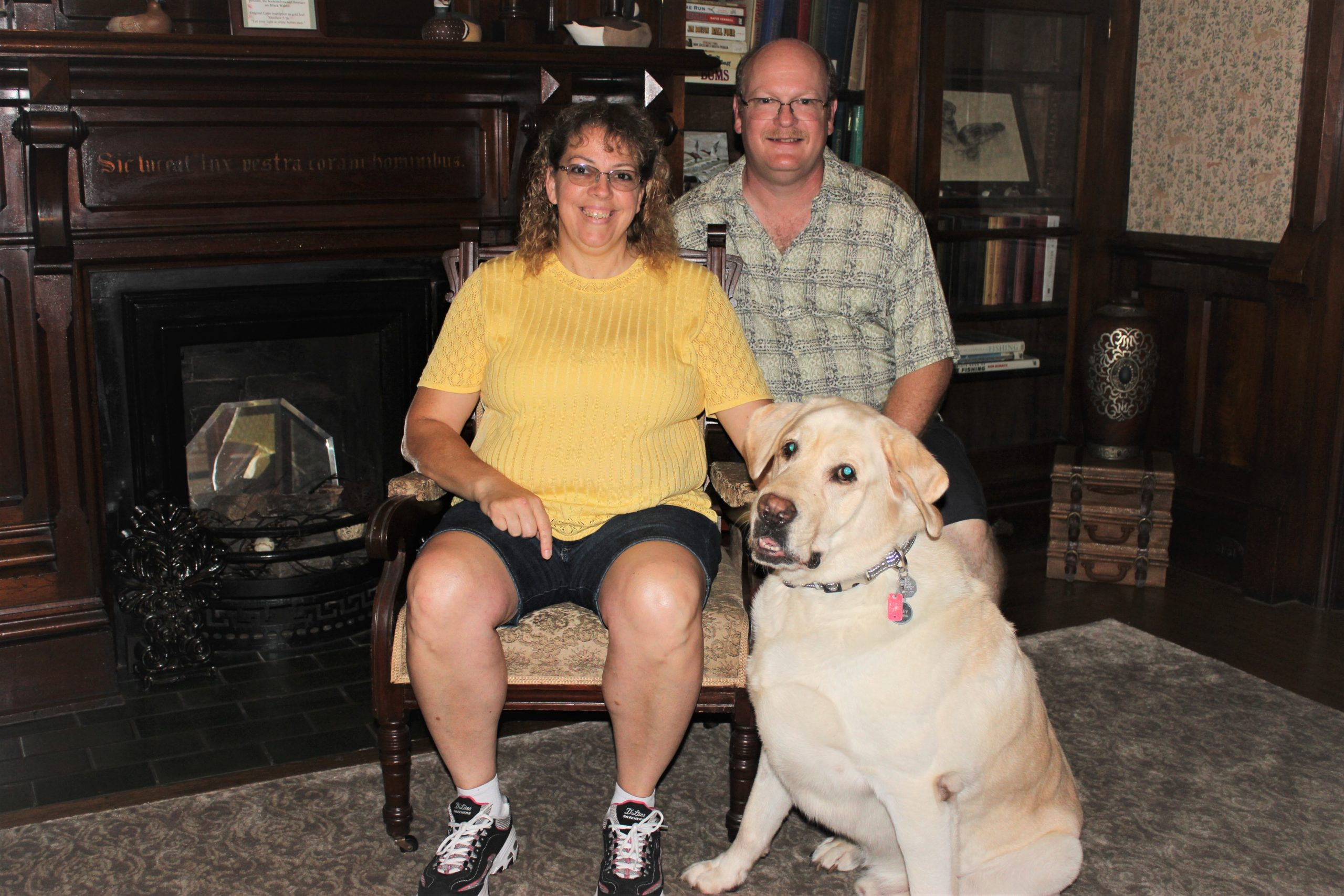 The Innkeepers, Steve and Lisa, with their dog Bailey in front of the Library Fireplce