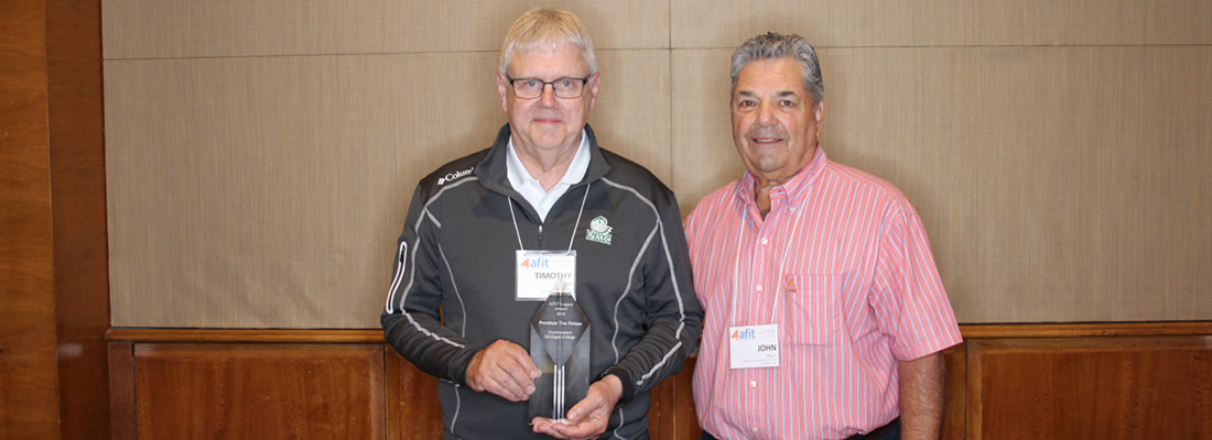 Northwestern Michigan College President Tim Nelson holding AFIT Legacy Award with AFIT Executive Director John Politi by his side.