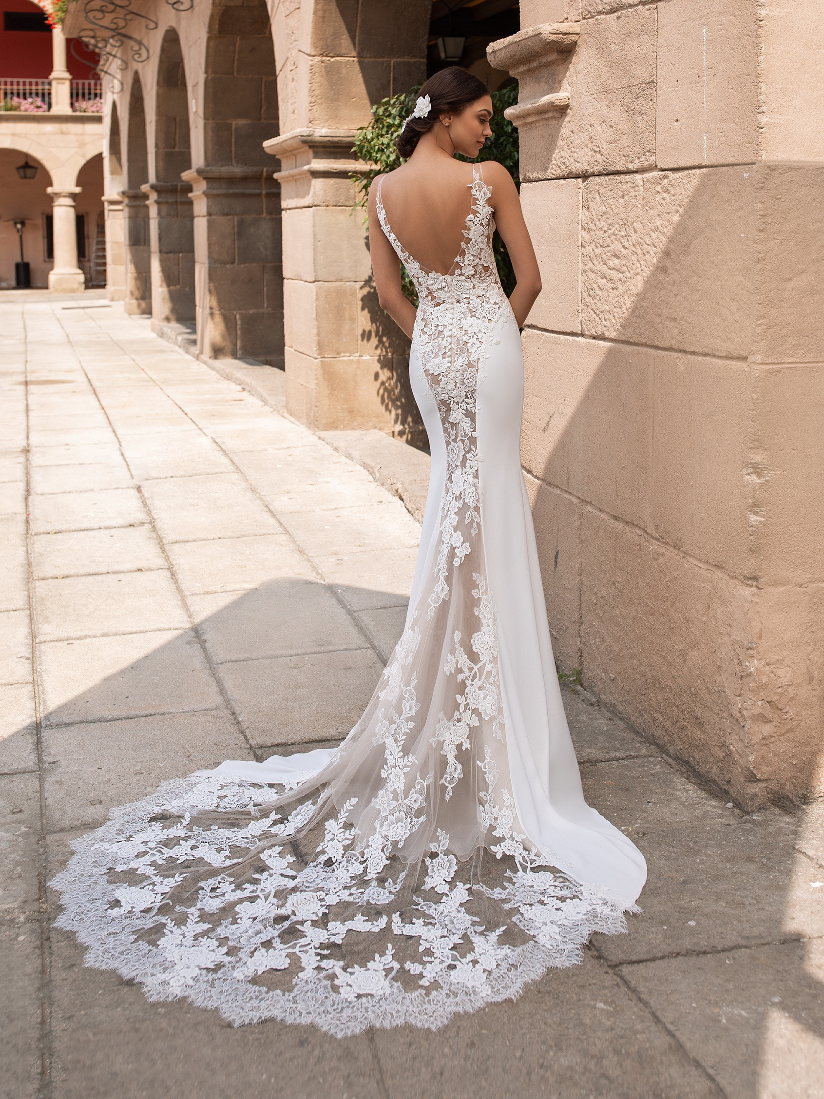 Bride using this sleek mermaid gown features a pure white, crepe façade and tulle, illusion paneling on the back, with carefully placed roses travelling from the straps down to the train's edge.