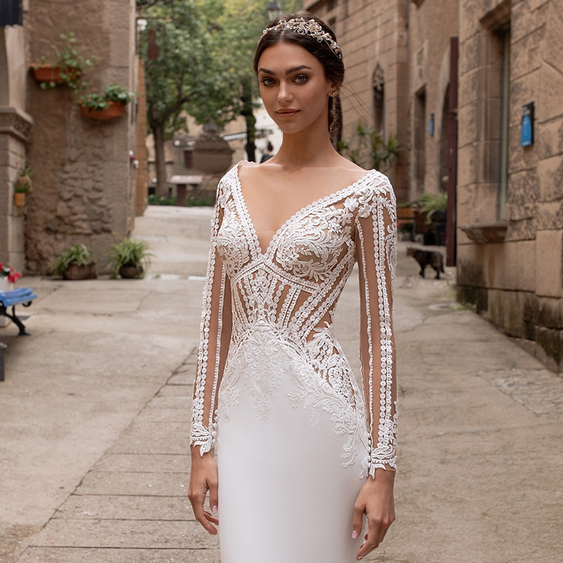 Bride using a geometrical cuts of eyelet lace trace the bust and hips of this artful bodice, blooming with leafy placements that line the angular waistline of the crepe mermaid skirt on both front and back