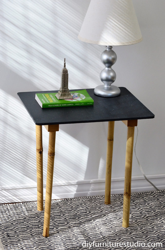 DIY side table made with a simple pine board table top and upcycled bamboo garden stakes legs.