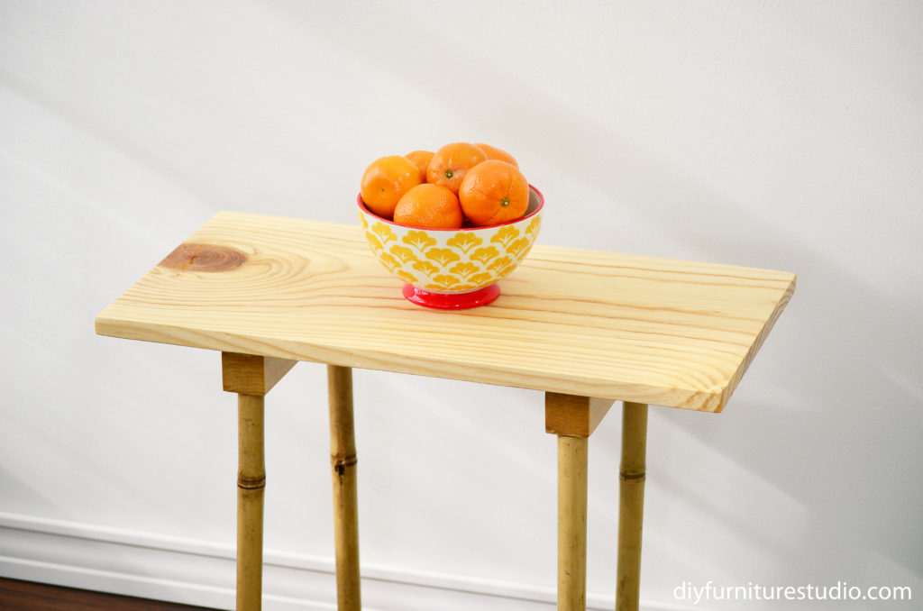 cropped view of DIY pine board and bamboo leg side table with bowl of oranges