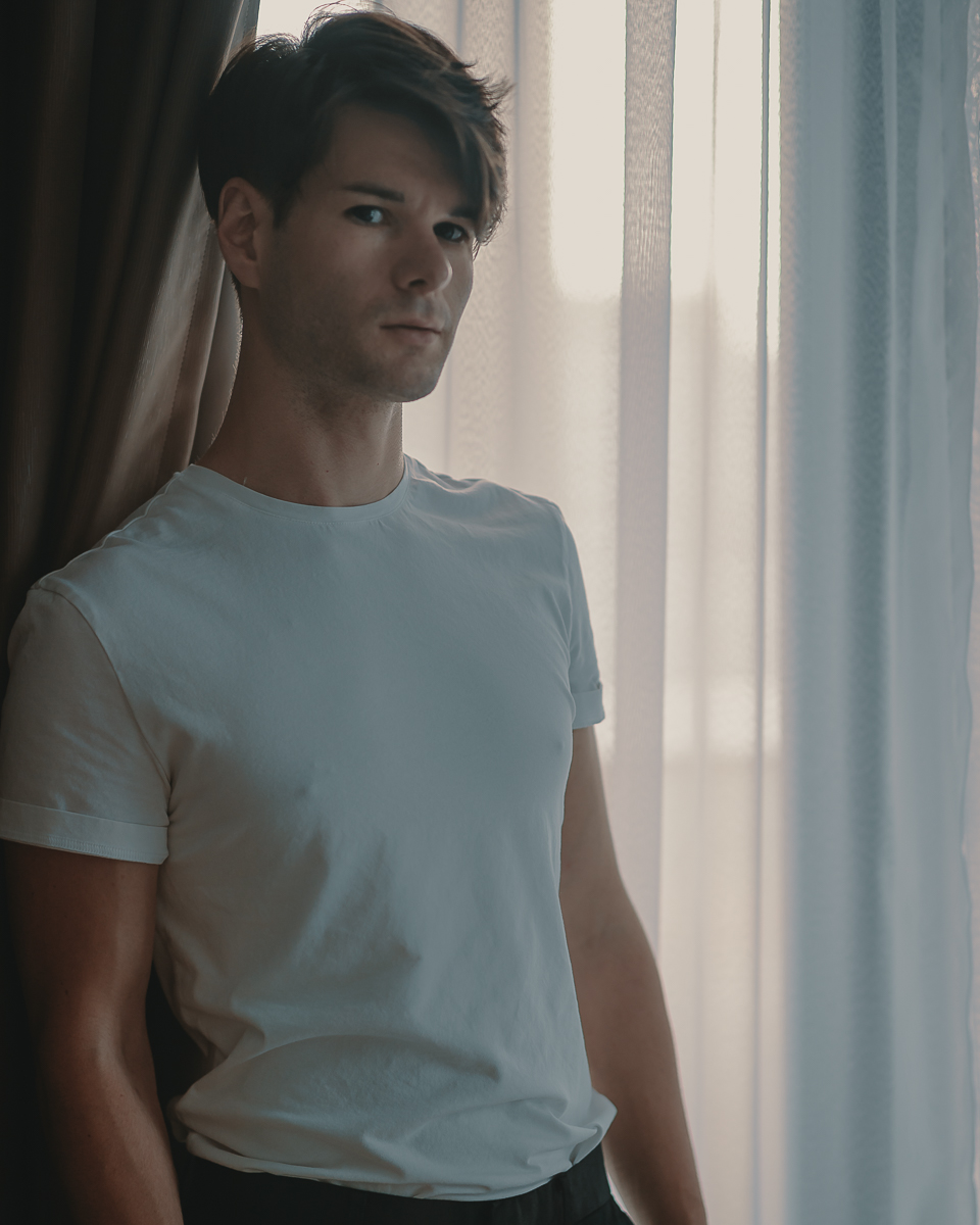 portrait of zaccy in a plain white t-shirt standing in front of a window