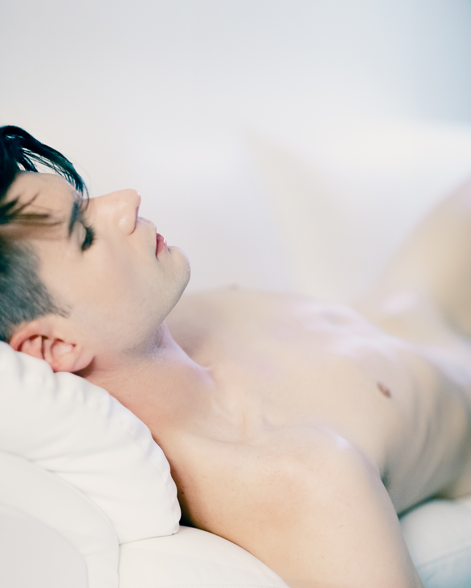 portrait of zaccy laying naked on a white couch