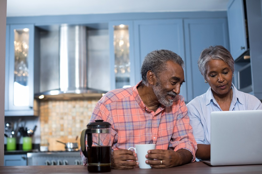 Couple looking at laptop in kitchen at home