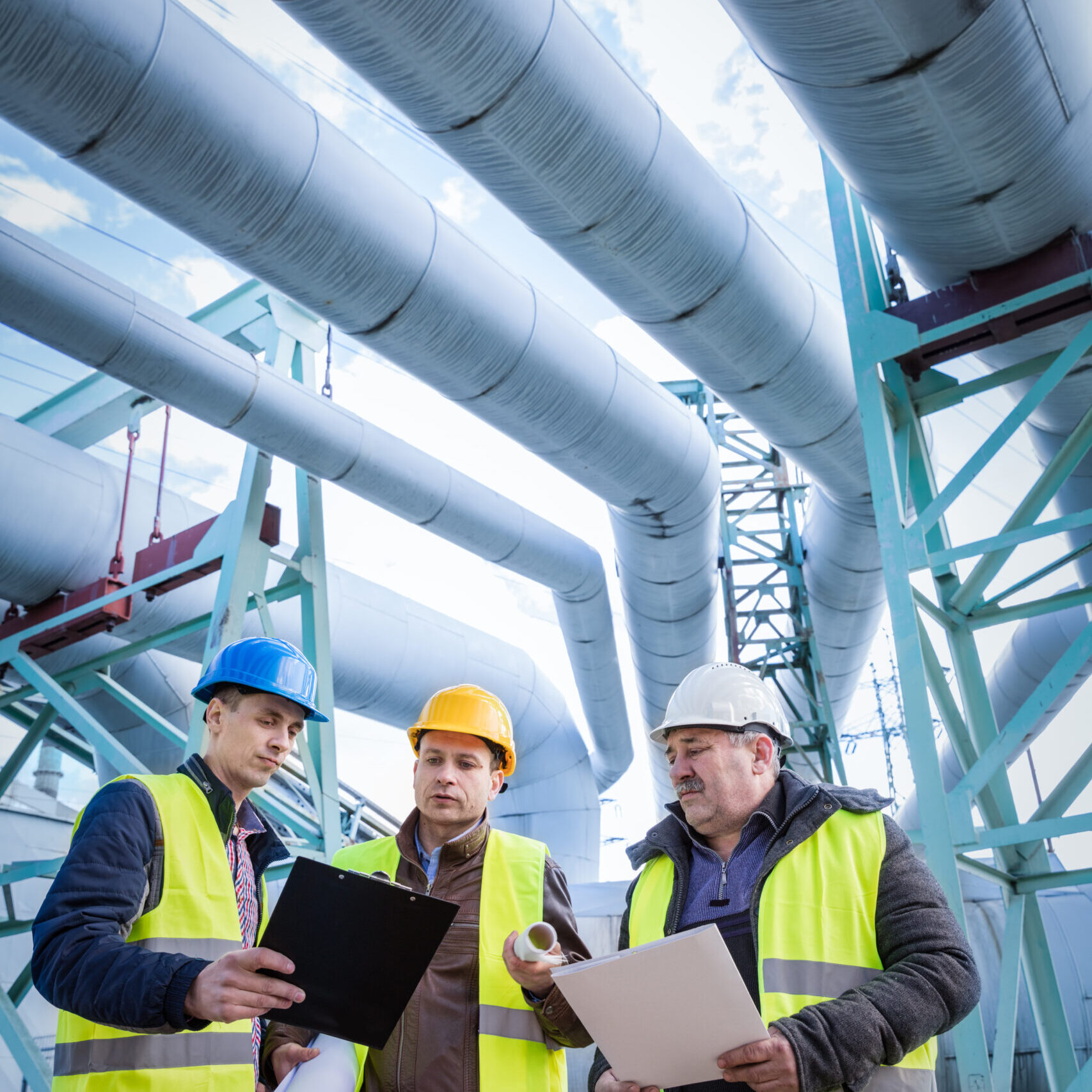 Engineers discussing maintenance of a petrochemical plant. Technical inspection. Oil and gas industry.