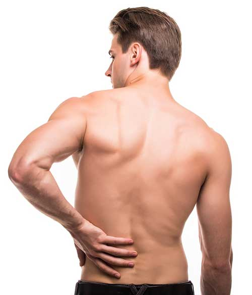 man rubbing his painful back