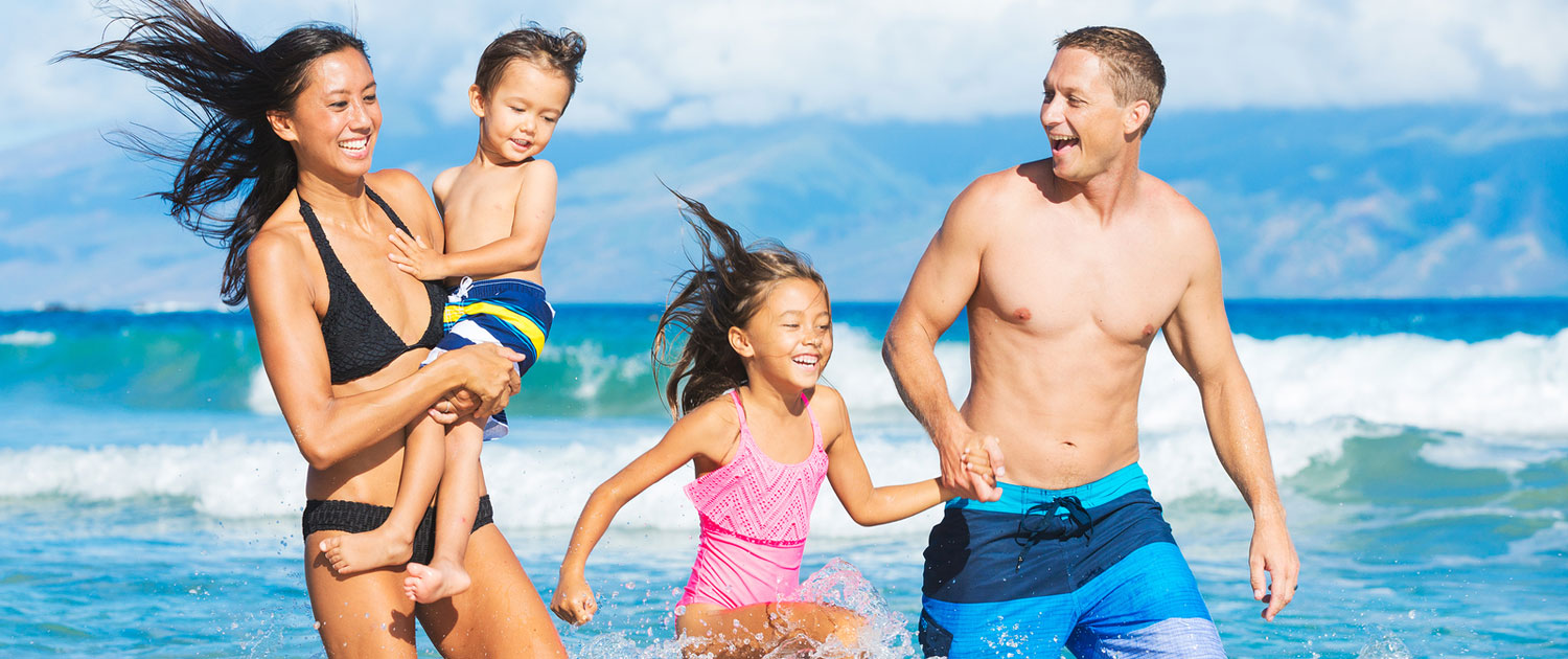 Happy Family of four plying in the water at the beach.