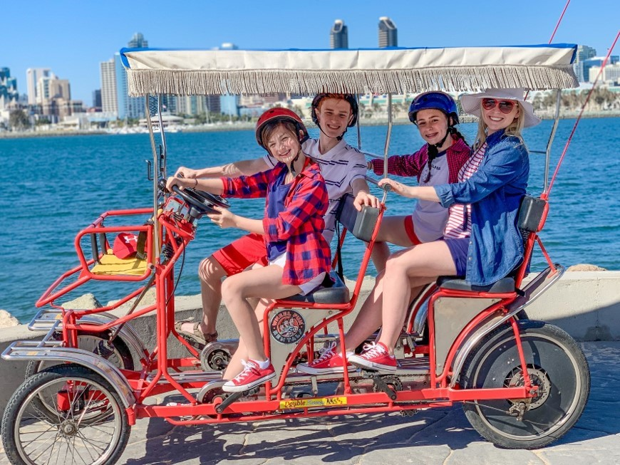 Family riding in a red six person surrey rented from Wheel Fun Rentals on Coronado Island. San Diego skyline in the backdrop