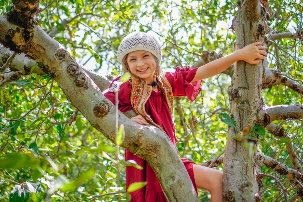 Young Girl pictured up in a tree resting on the tree limbs. Climbing trees is a time-honored childhood tradition and about as back-to-basics as summer fun gets. Go out on a limb and pretend you are still that monkey-kid you used to be and race your kids to the tippy top.