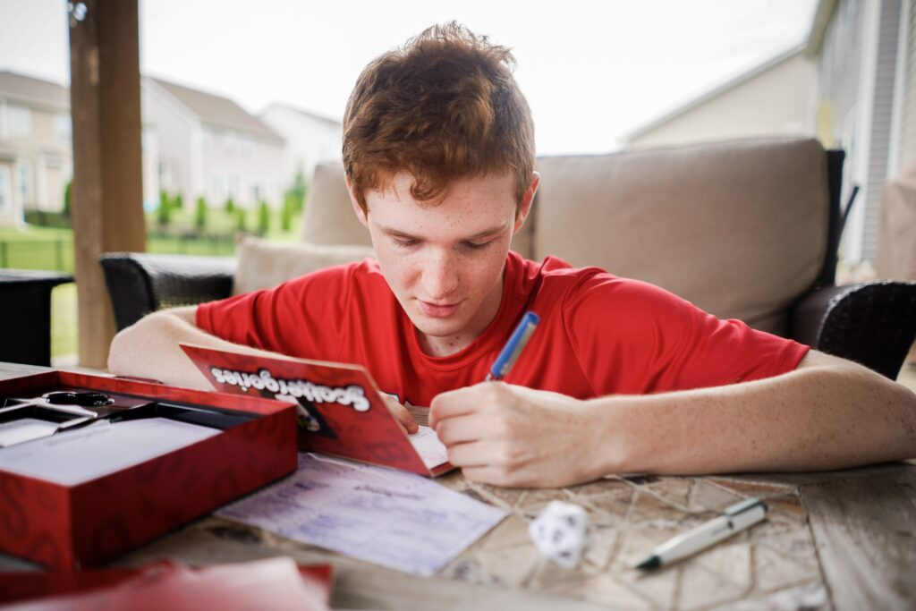 Photo of teen boy playing Scattergories. - Safe Summer Bucket List – 100 Ways to Have Fun This Summer While Social Distancing