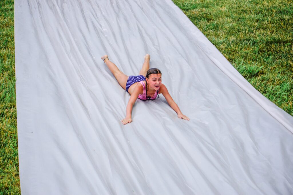 Girl slides down a large slip and slide. Slip 'n slides are a fun way to cool off on a hot summer day, no matter what age you are. Try making your own with a large roll of clear or white heavy duty plastic sheeting so that it doesn't get hot and landscaping stakes to hold it in place. Just add water and some Dawn dish soap and you are ready to go! - Safe Summer Bucket List – 100 Ways to Have Fun This Summer While Social Distancing