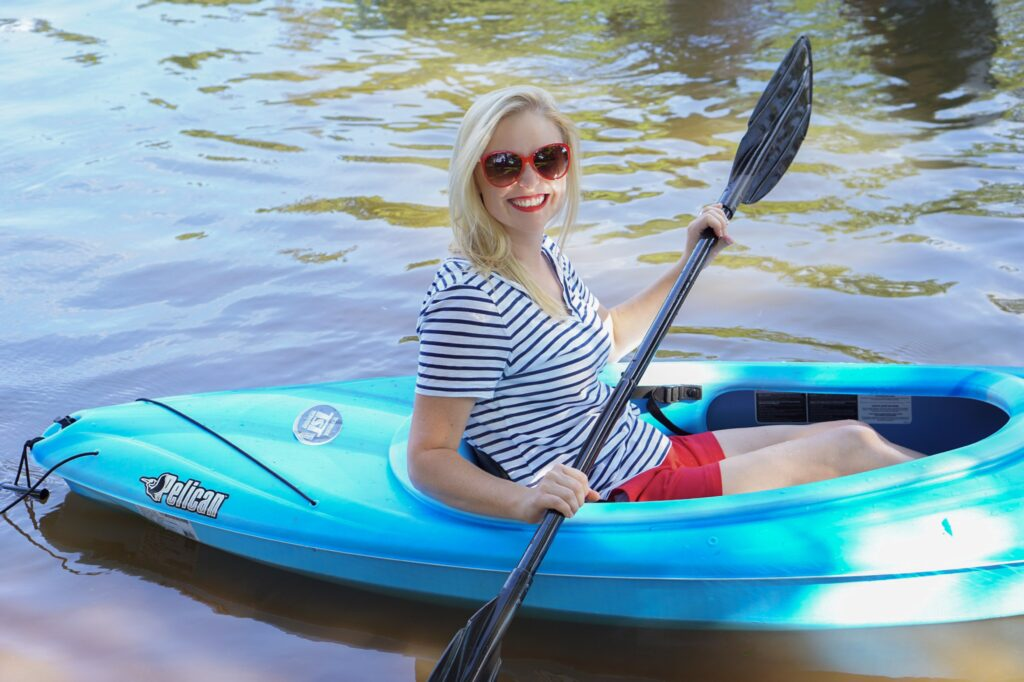 Woman in blue kayak paddles through a river. - Safe Summer Bucket List – 100 Ways to Have Fun This Summer While Social Distancing