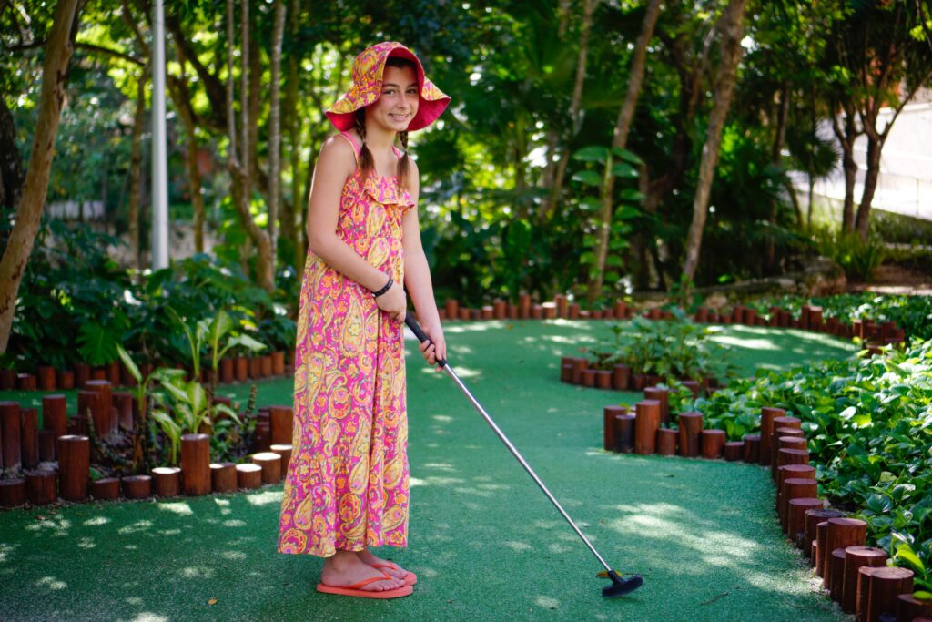 Girl pictured playing putt-putt golf. playing putt-putt golf could be a great way to get out of the house with kids while social distancing. Just be sure to wait your turn for each hole and keep a good pace. - Safe Summer Bucket List – 100 Ways to Have Fun This Summer While Social Distancing