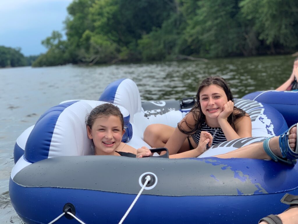 Two girls spend a relaxing summer day slow tubing down a river in rafts. - Safe Summer Bucket List – 100 Ways to Have Fun This Summer While Social Distancing