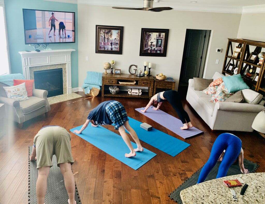 Family practicing yoga on mats in living room of house. Clear your couches to the side and lay down some yoga mats and start your day off with some movement and mindfulness.