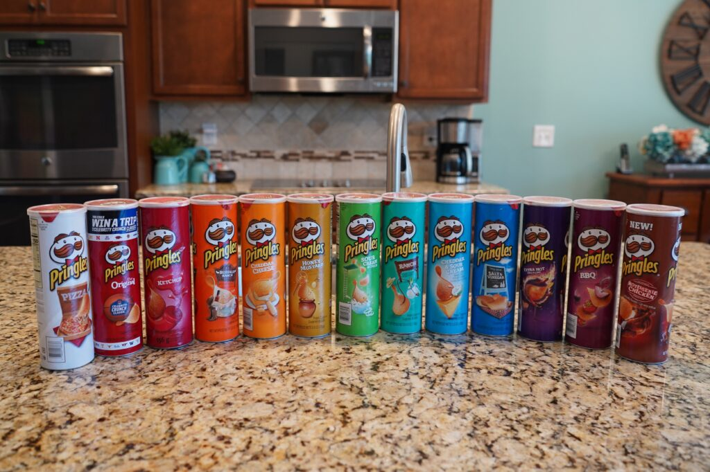 Various flavors of Pringles Potato chips ready for a blind taste test. Prepare an assortment of different foods with the same theme such as fruit or chips and have your family taste them blindfolded and try to guess what they are. Our favorite blind taste test is the Pringles Challenge.