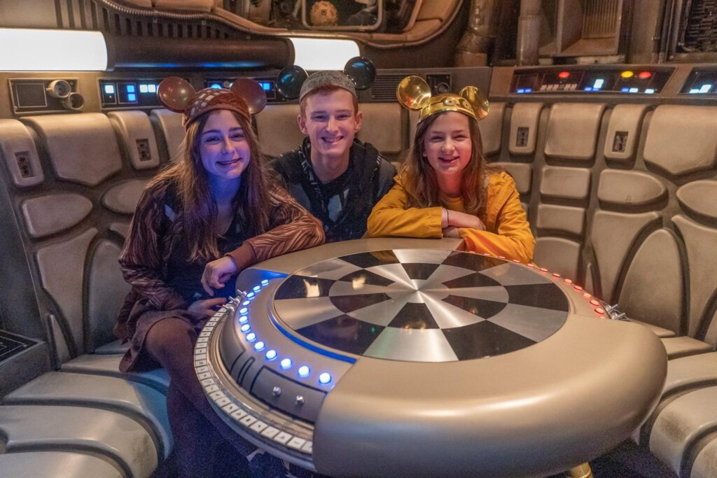 "Kids pose with a with a Dejarik ""holo-chess"" table. Before getting into the cockpit, riders are led into the lounge of the Millennium Falcon. This is a great opportunity to grab some quick photos while you wait in the ride's immersive queue area."