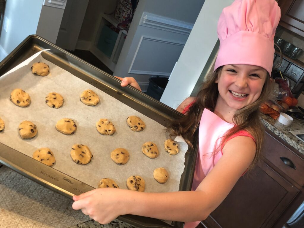 Smiling girl holding pan of cookie dough ready to go in the oven. Get out those cook books and try baking something you've never made before.- Safe Summer Bucket List – 100 Ways to Have Fun This Summer While Social Distancing