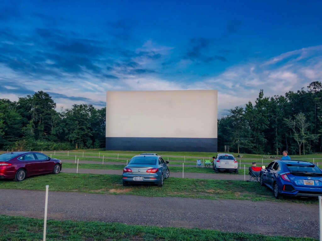 Image of movie screen at at Drive-In Movie Theater. Drive-ins are making quite a comeback as one of the best ways to enjoy a summer blockbuster while social distancing! We are lucky enough to have one within driving distance that offers movies in high definition.