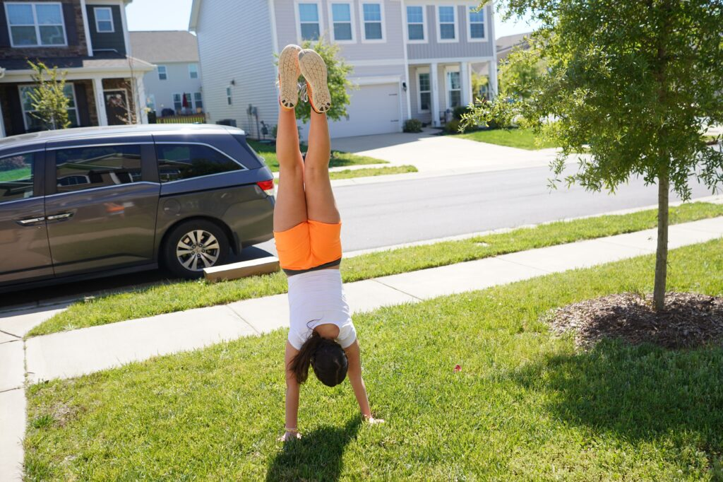Girlpractices hand stand on the lawn in front of home. earn to cartwheel and flip this summer on a trampoline or on the lawn. Solid gymnastics skills can take weeks to fully perfect so make sure you are on hand to spot and supervise.