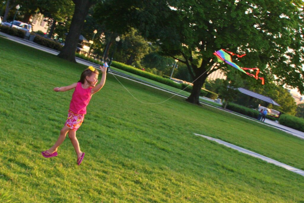 Young girl flies a rainbow kite in an open field. - Safe Summer Bucket List – 100 Ways to Have Fun This Summer While Social Distancing