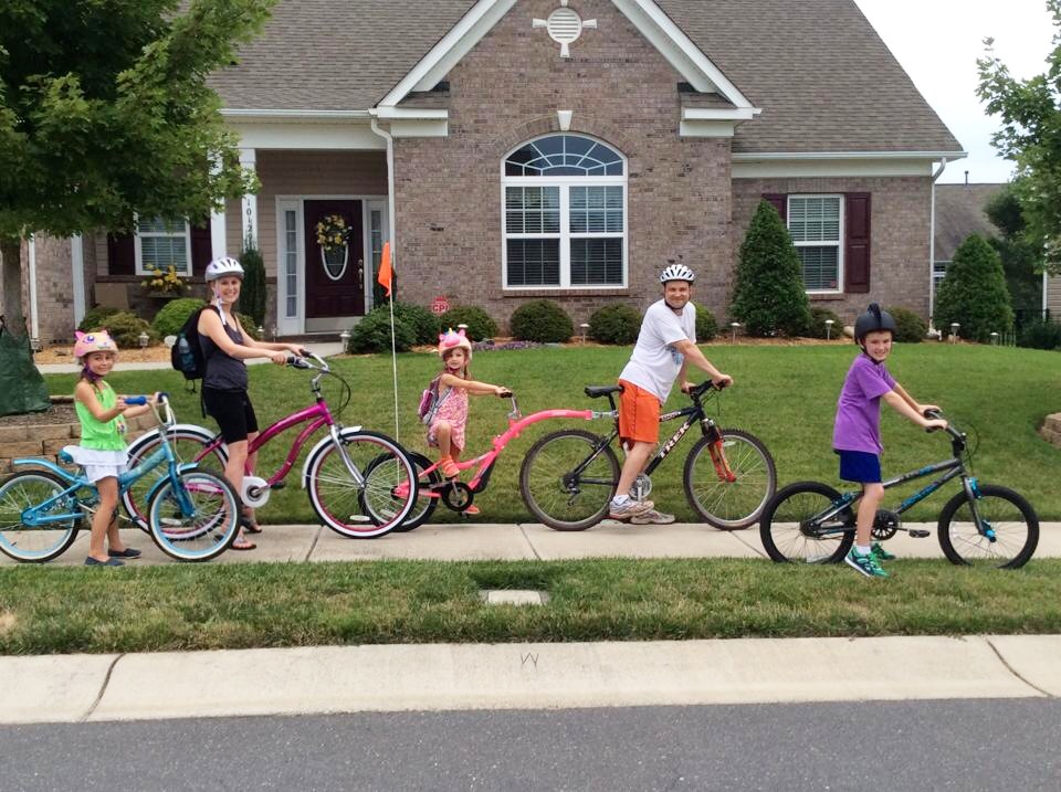 Family of five out on bike ride in neighborhood. Biking with the family in your neighborhood or local greenway can be a great safe option to get everyone moving.- Safe Summer Bucket List – 100 Ways to Have Fun This Summer While Social Distancing