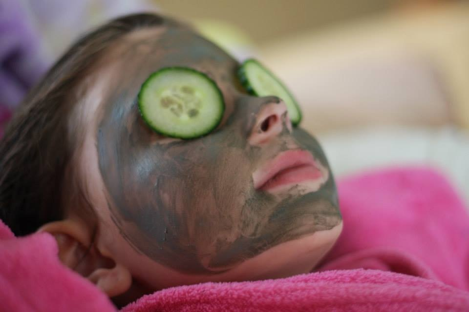 "Young girl with cucumbers over her eyes and face mask relaxes during a ""spa day"". Get out the bath salts, nail polish and clay masks and enjoy a little spa time for everyone. You can take turns doing each other's manicures and pedicures or just relax with some hot towels, cucumber eye pads, and candles. Whatever makes you feel pampered!"