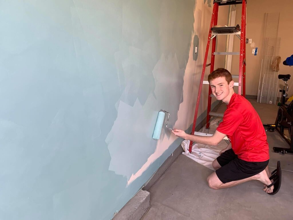 Teenage boy paints wall as part of room make-over. - Safe Summer Bucket List – 100 Ways to Have Fun This Summer While Social Distancing