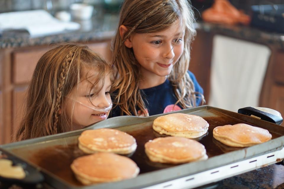 Young girls eye pancakes in the griddle with delighted expectation. Whether it's trying out Eggs Benedict or making a big pile of pancakes on the griddle, it can be fun to change things up and surprise the kids!