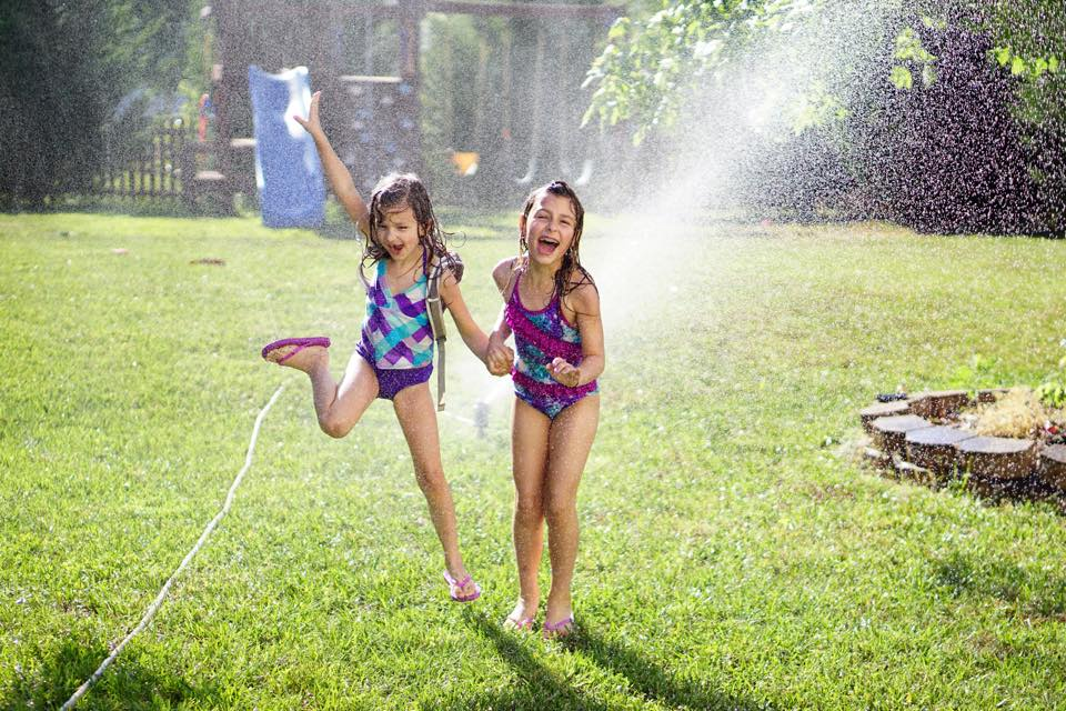 Young girls runs through the sprinklers in back yard on a hot day. - Safe Summer Bucket List – 100 Ways to Have Fun This Summer While Social Distancing