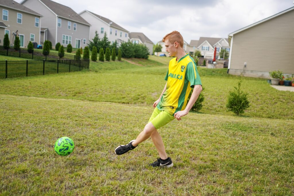 Boy kicks a soccer ball around in the back yard. Head outside with the kids to shoot some hoops, kick around the soccer ball or play some catch. We also love a good game of tennis or ping pong.