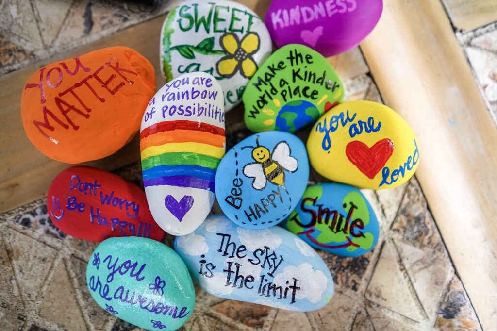 Pile of rocks painted with encouraging messages. Paint rocks with encouraging messages and fun designs and then hide them around your neighborhood or a local nature trail for others to find.