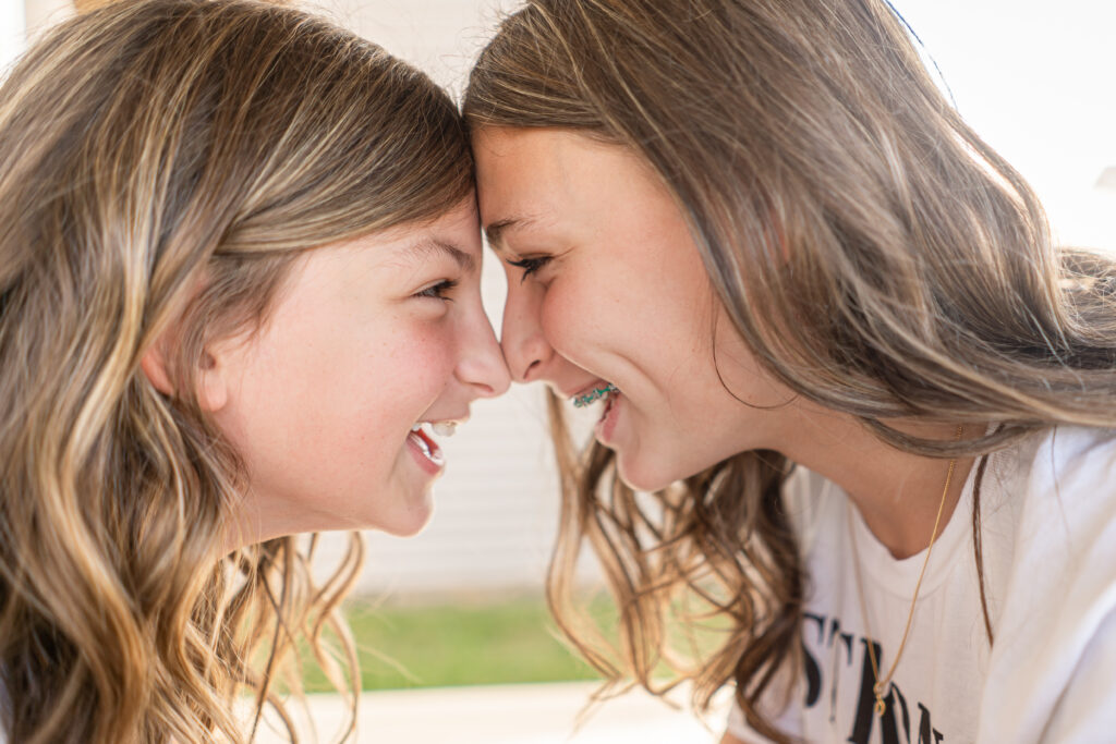 Sisters smiling at each other. - Safe Summer Bucket List – 100 Ways to Have Fun This Summer While Social Distancing
