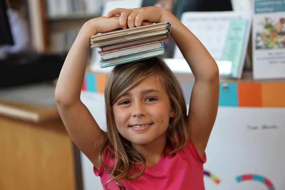 Girl balances pile of books on her head. - Safe Summer Bucket List – 100 Ways to Have Fun This Summer While Social Distancing