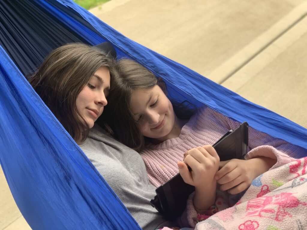 Two girls hanging out in a hammock watching ipad. - Safe Summer Bucket List – 100 Ways to Have Fun This Summer While Social Distancing