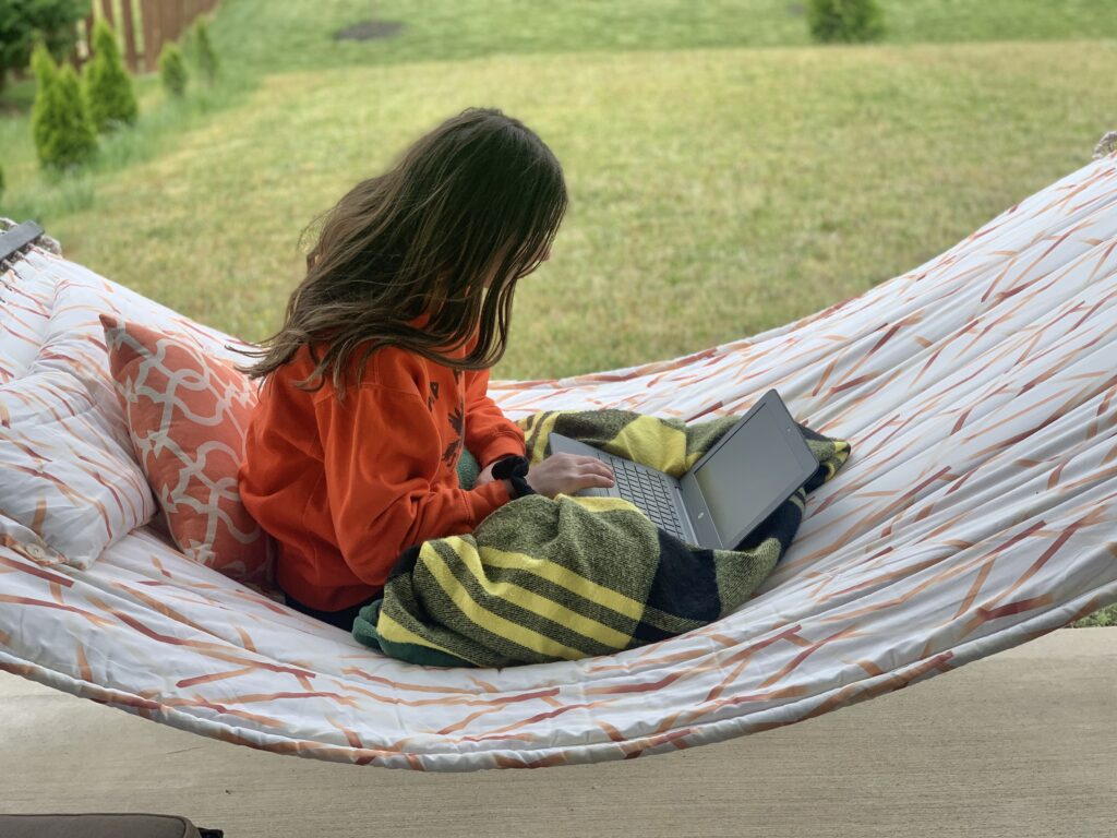 Girl sitting in hammock works on online class.  Just because school is out doesn't mean learning has to stop. Take this time to learn a new skill or hobby, study a new subject or re-learn an old one.