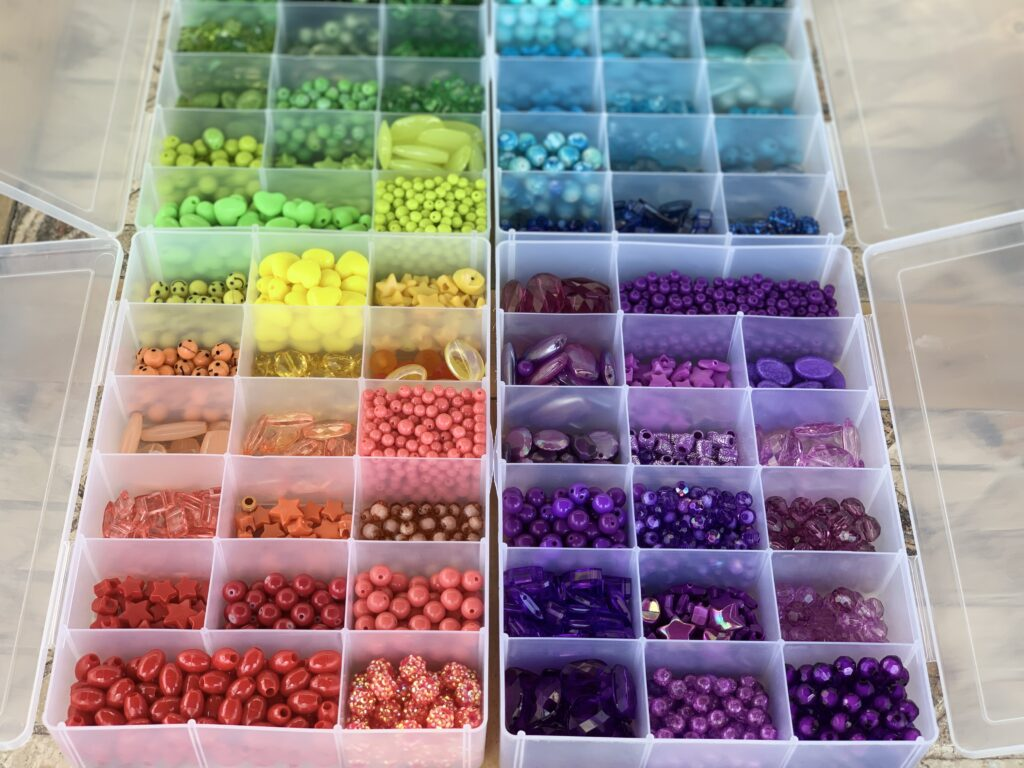 Bins filled with colorful beads. A jewelry craft encourages creative expression and leaves you with a fun finished product of your design. - Safe Summer Bucket List – 100 Ways to Have Fun This Summer While Social Distancing