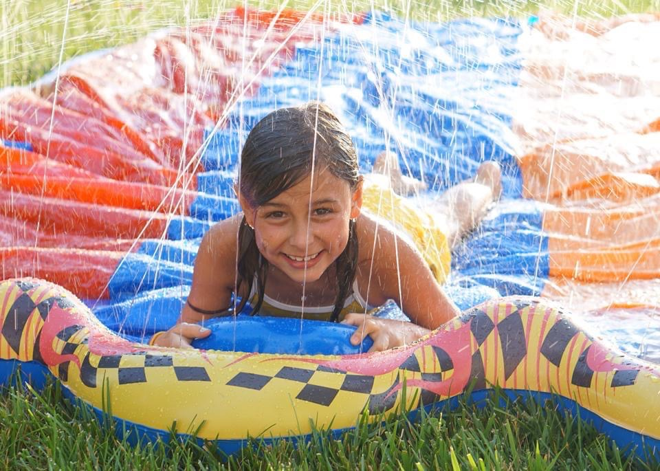 Girl smiles happily on colorful slip and slide.